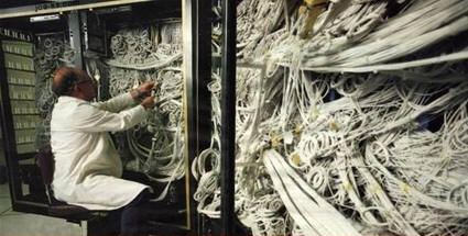 Man fiddling with a mess of cables.